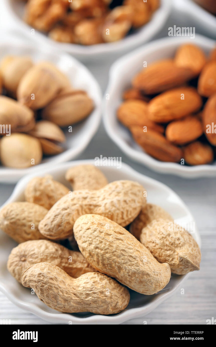 Peanuts, pistachios, almonds and walnut kernels in the bowls, close-up Stock Photo