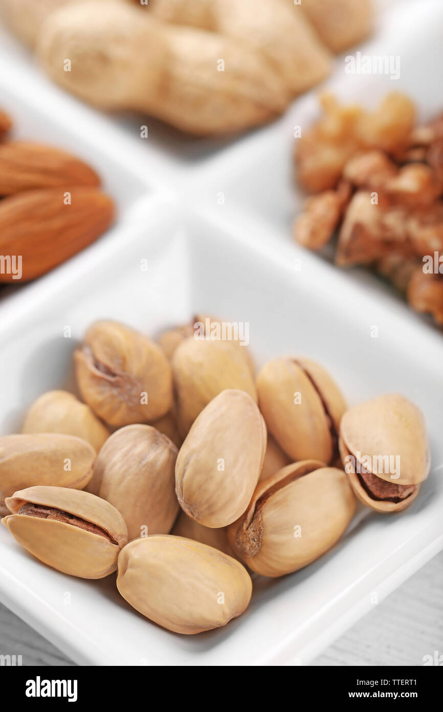 Walnut kernels, almonds, pistachios, peanuts in the ceramic rectangle plate, close-up Stock Photo