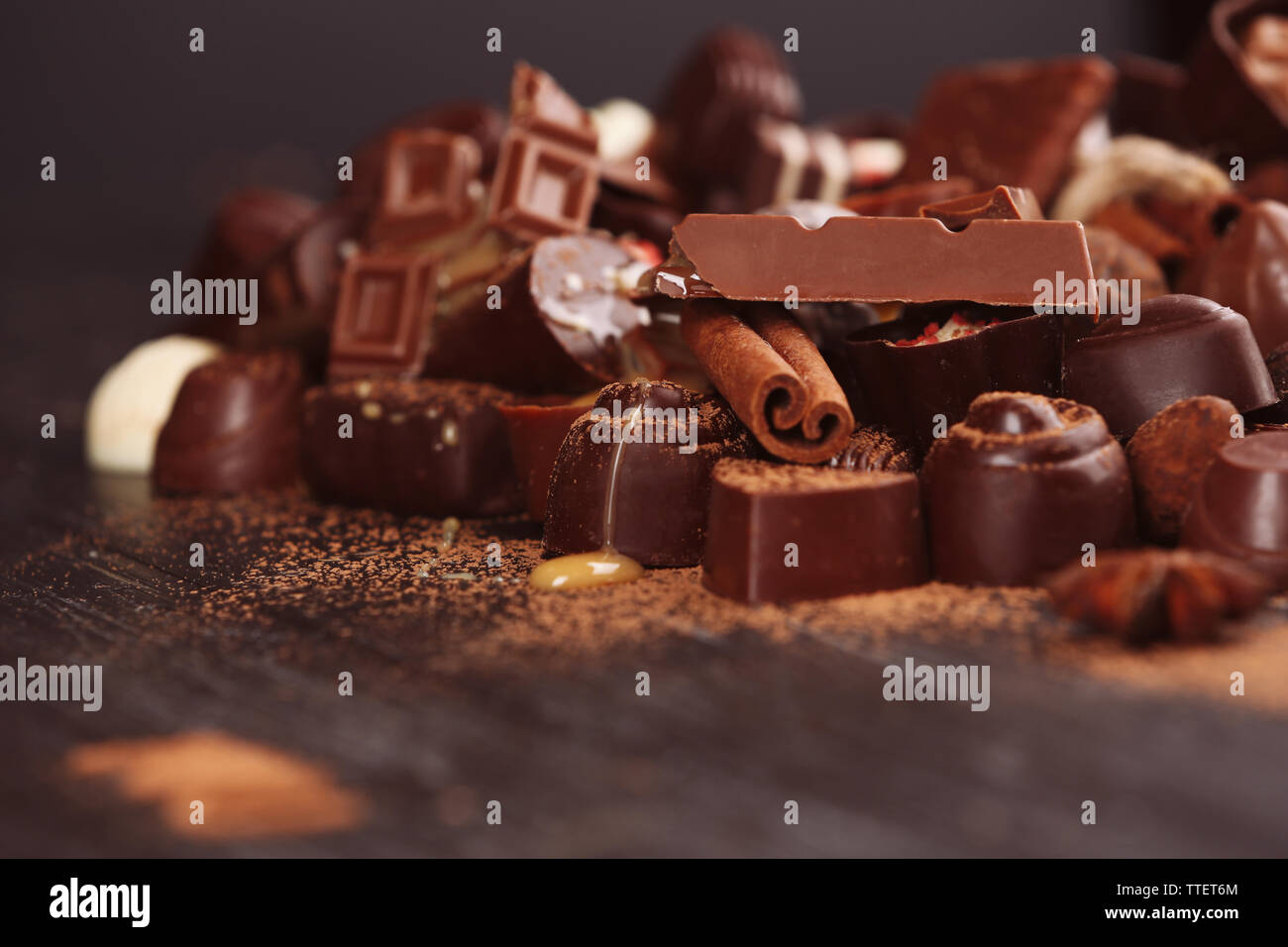 Assortment of tasty chocolate candies and cinnamon on wooden table background - Stock Image