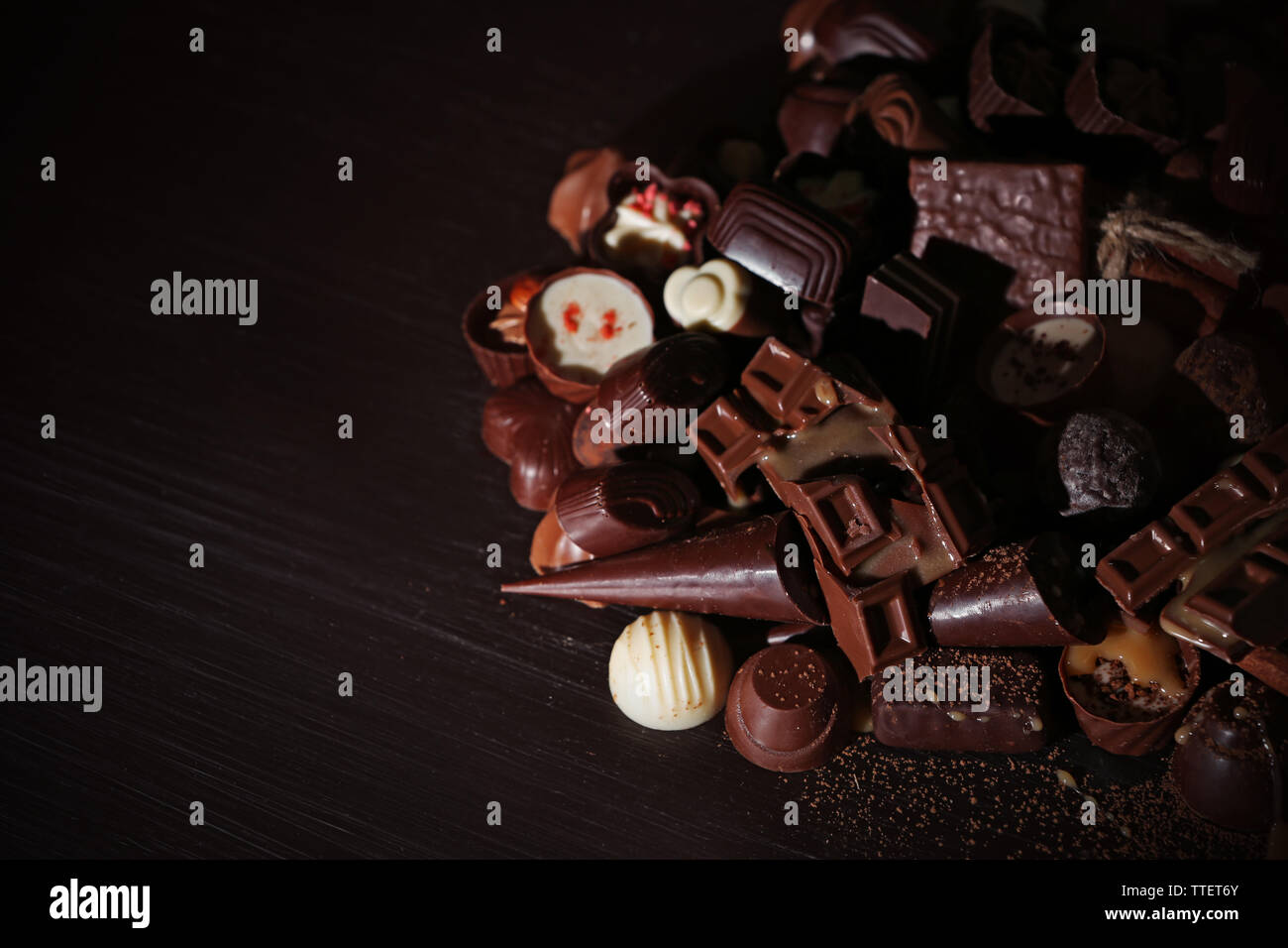 Assortment of tasty chocolate candies on wooden table background - Stock Image