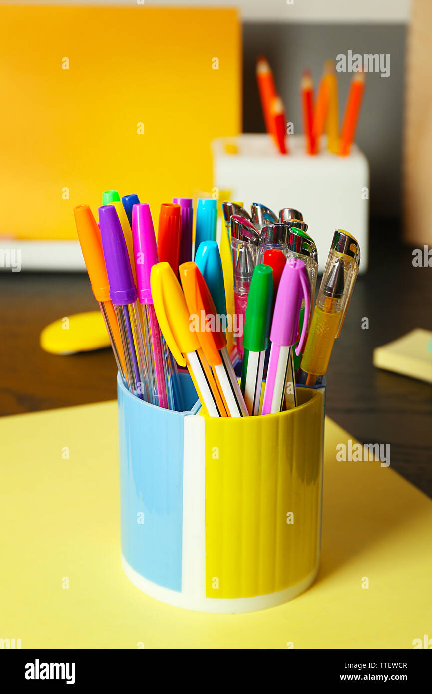 Set Of Colored Pens In Glass On Black Table Close Up Stock