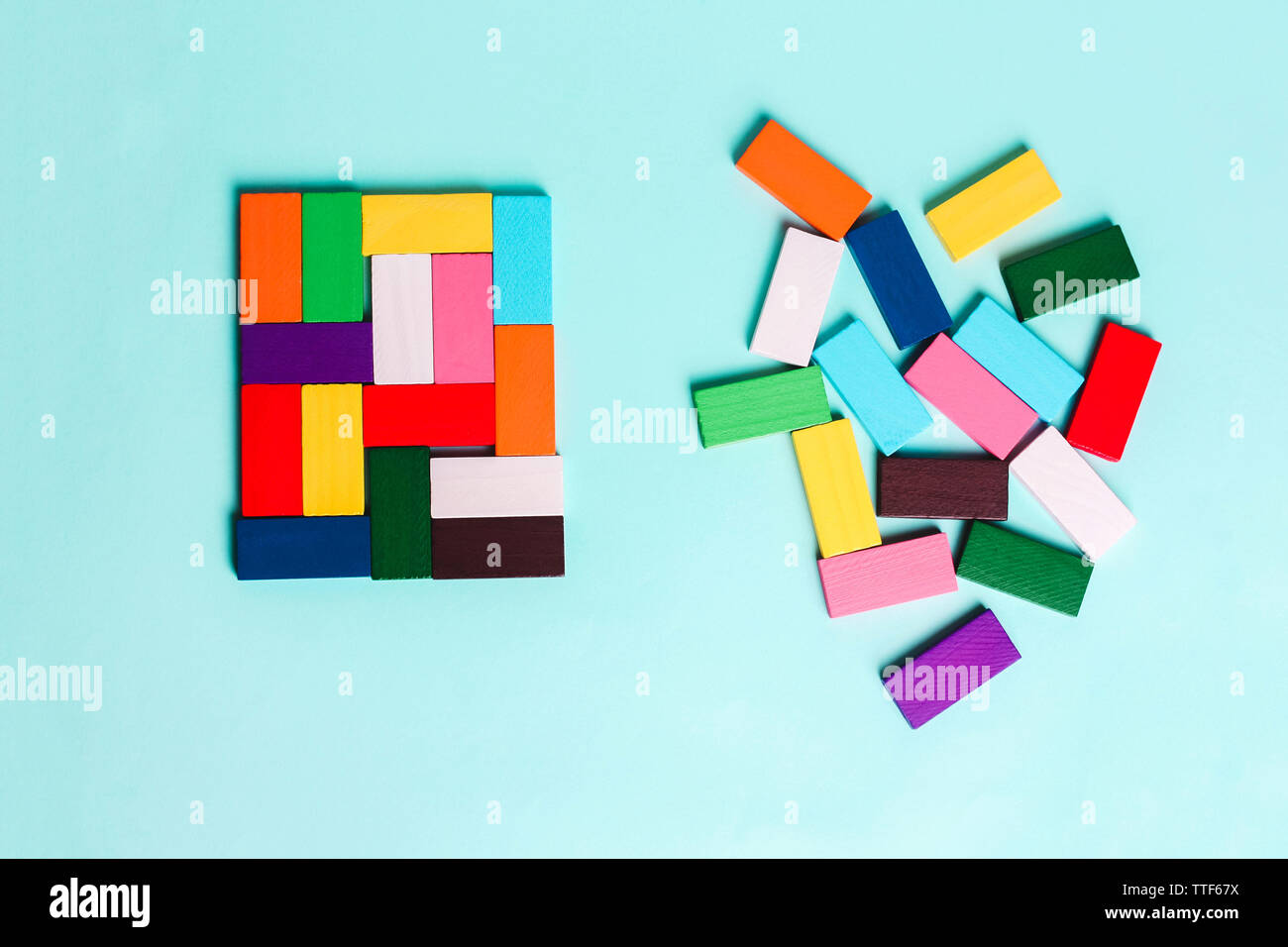 order and chaos. Chaotic unorganized colored dominoes and ordered. Concept of business model, organization. Left and right hemisphere of the brain. - Stock Image