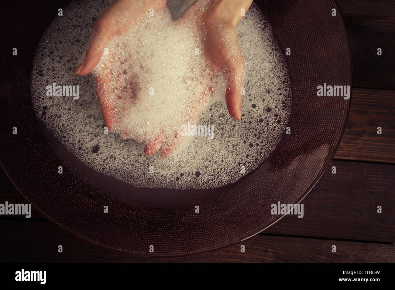 Woman washing hands in bowl on wooden background - Stock Image