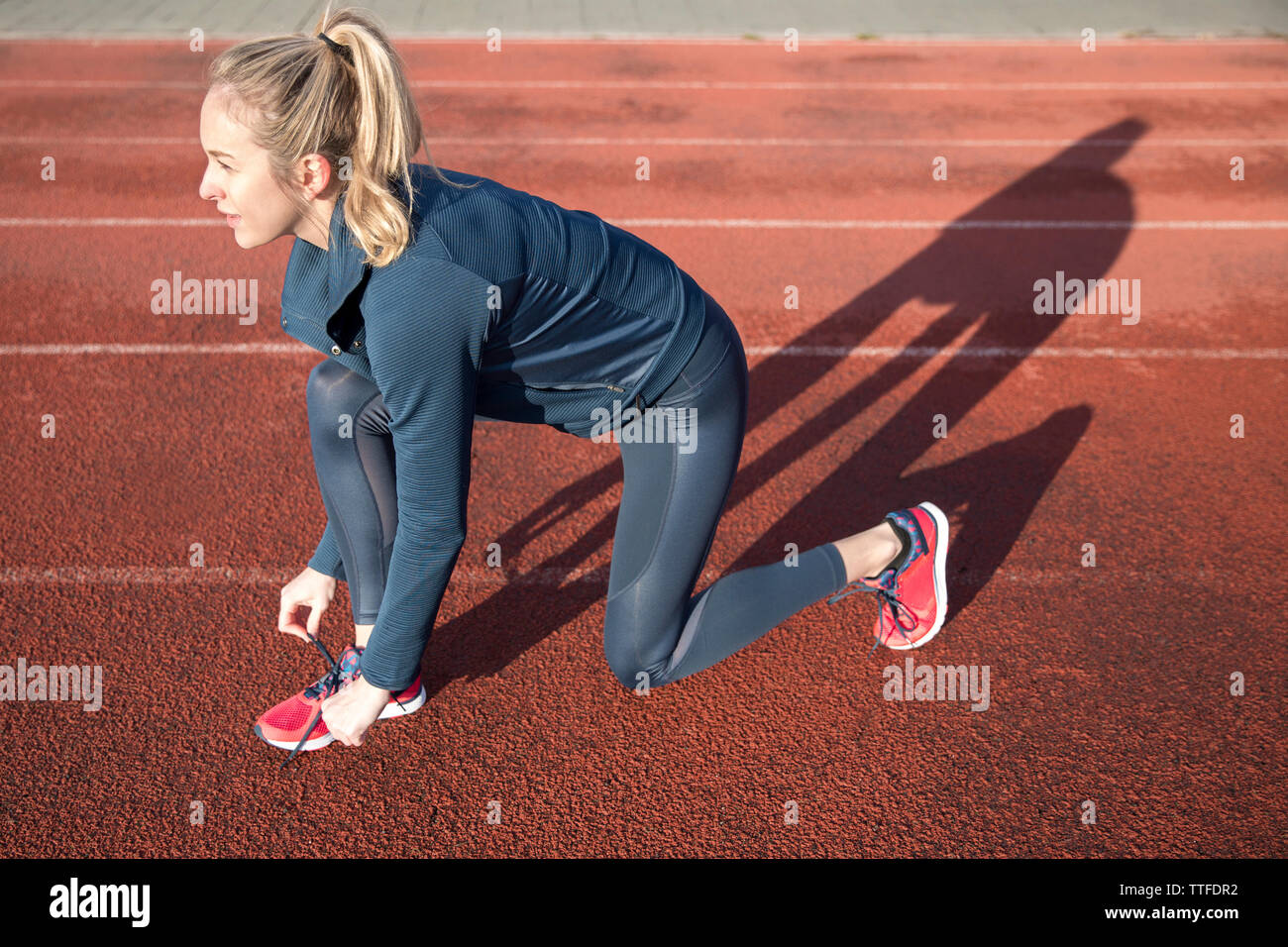 Side view of female athlete tying shoelace on sports track - Stock Image