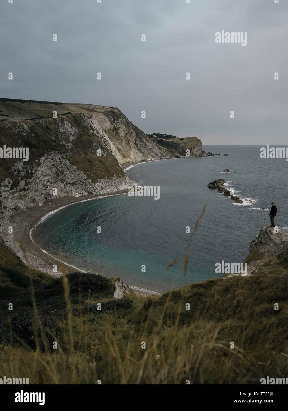 A man stands on a rock on the background of the bay Durdle Door - Stock Image