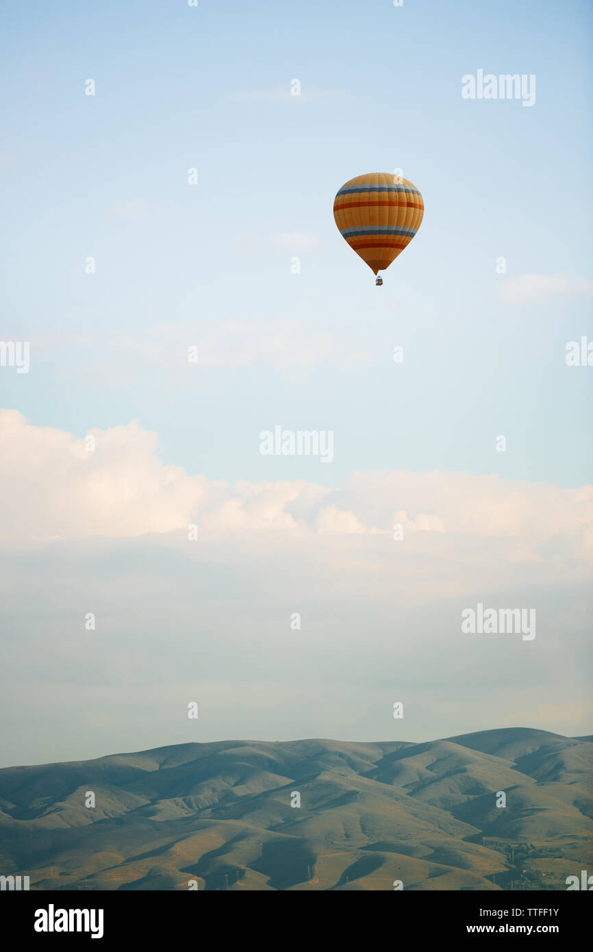 Hot air balloon flying over the hills - Stock Image