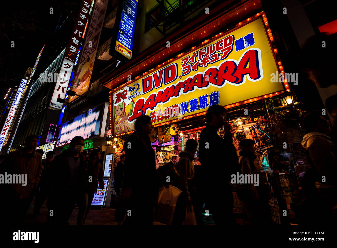 Shoppers pass a multimedia shop in Akihabara, Tokyo - Stock Image