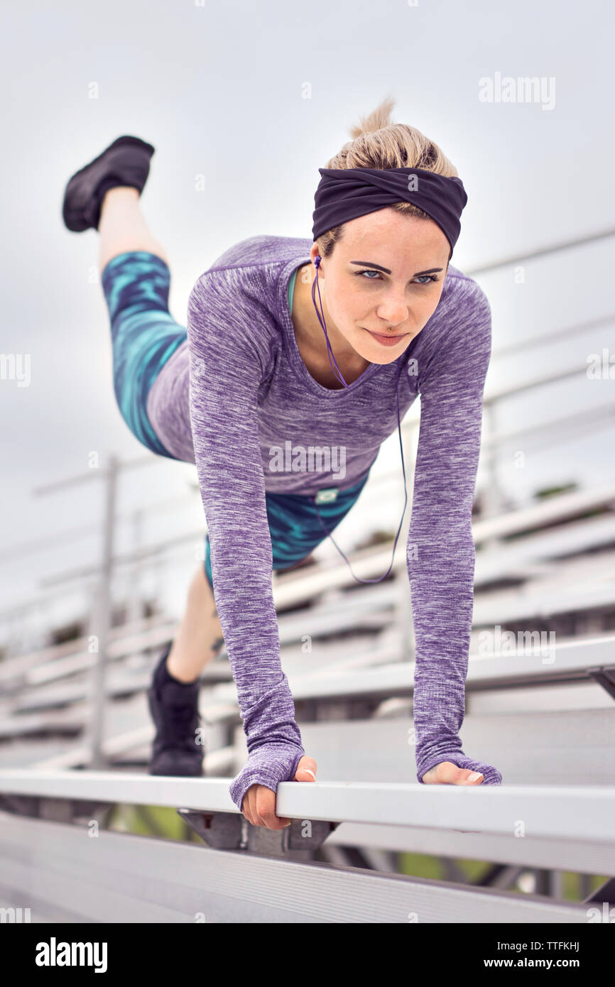 Motivated tattoed female working out Stock Photo