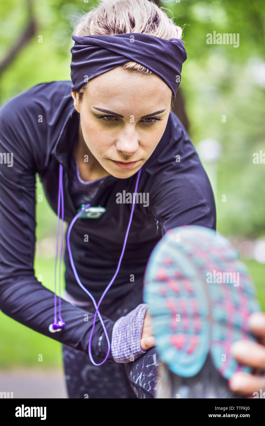 Athletic female stretching leg during daily workout Stock Photo