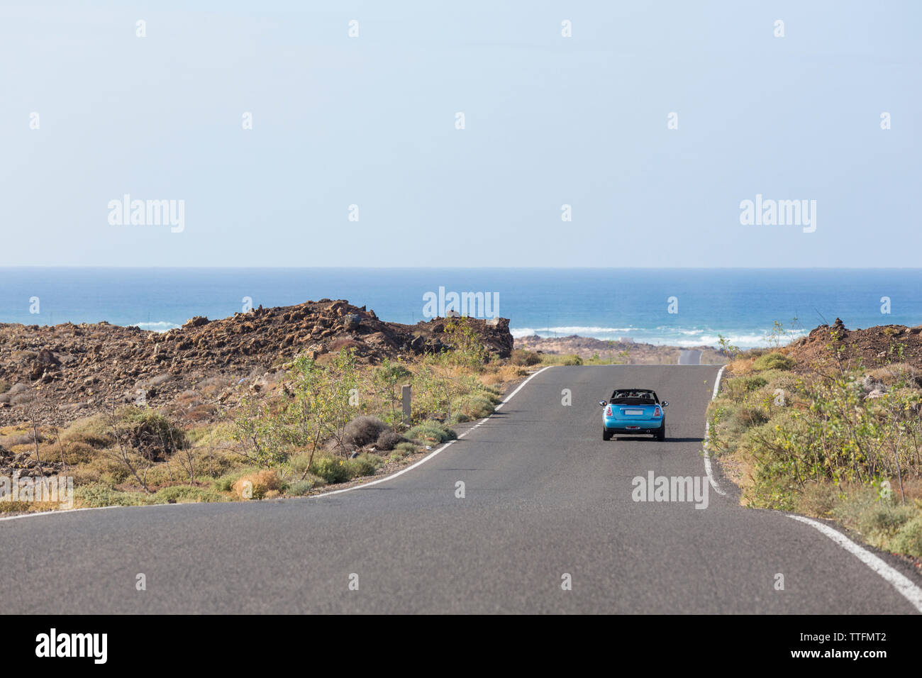 Blue cabrio car driving in empty paved road towards the ocean - Stock Image