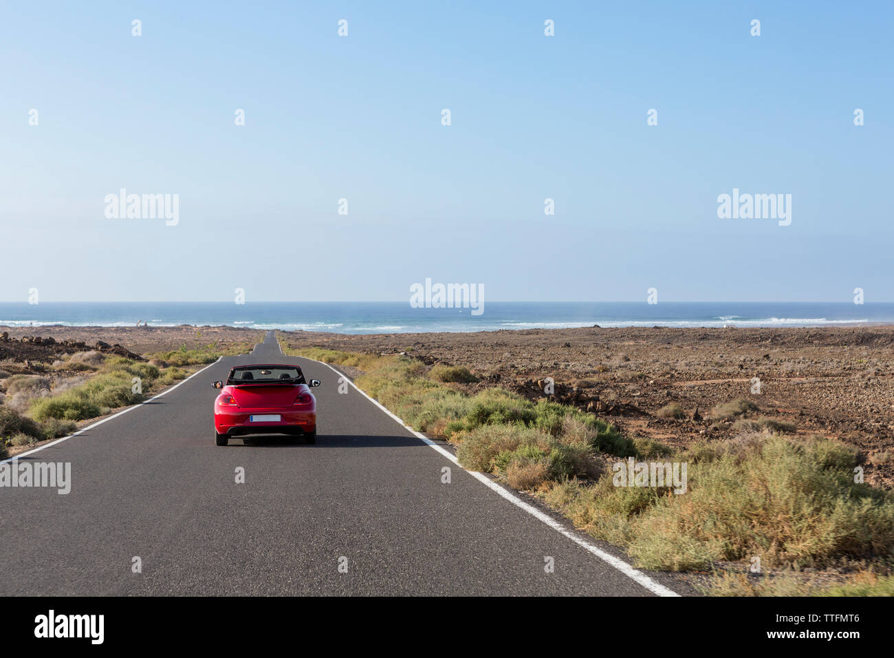 Red cabrio car driving in empty paved road towards the ocean - Stock Image