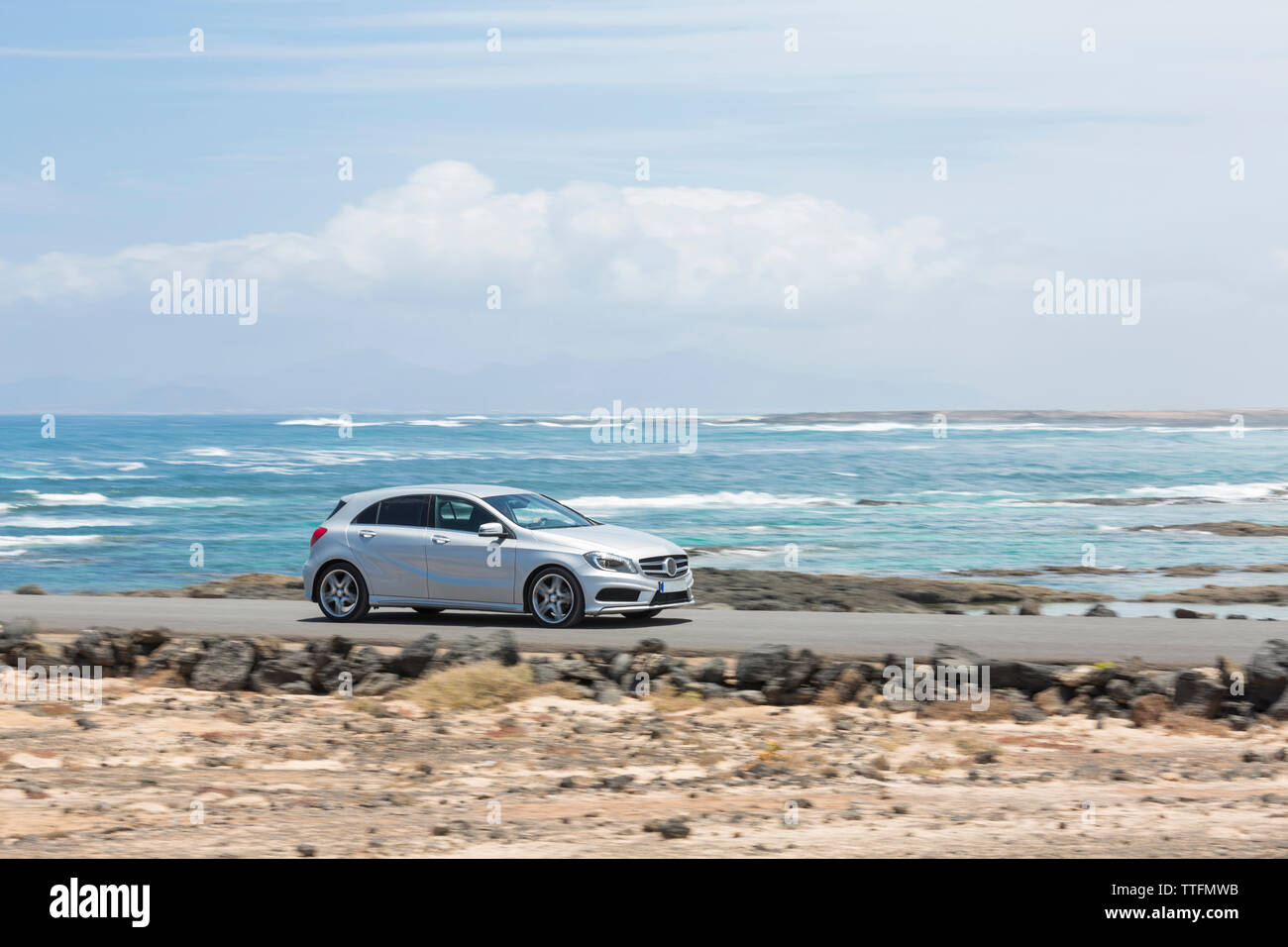 Grey car driving empty paved road with ocean in the background - Stock Image