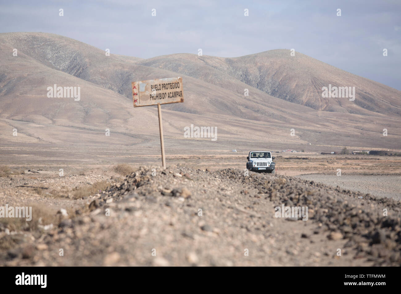 White jeep 4x4 driving off road  empty dirty road in desert landscape - Stock Image