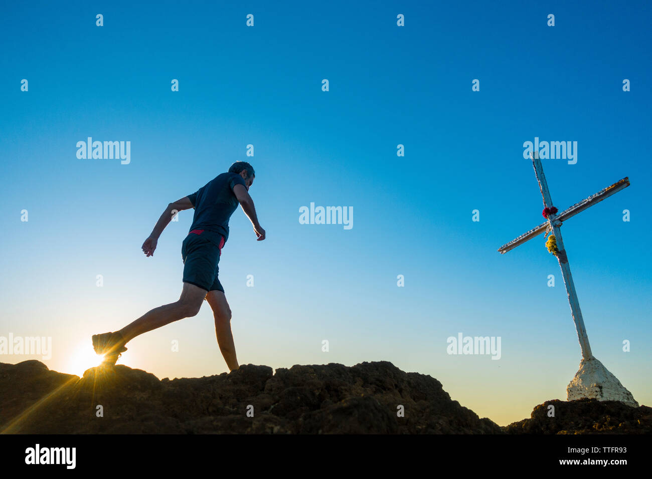 Gran Canaria, Canary Islands, Spain. 17th June 2019. Trail runner on mountain summit as the sun rises into a cloudless sky on a glorious Monday morning on Gran Canaria. Credit:Alan Dawson/Alamy Live News. - Stock Image