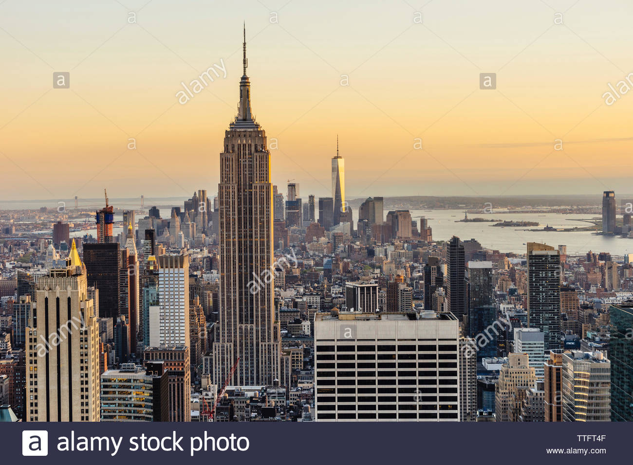 Empire State Building and One World Trade Center in city against sky during sunset - Stock Image