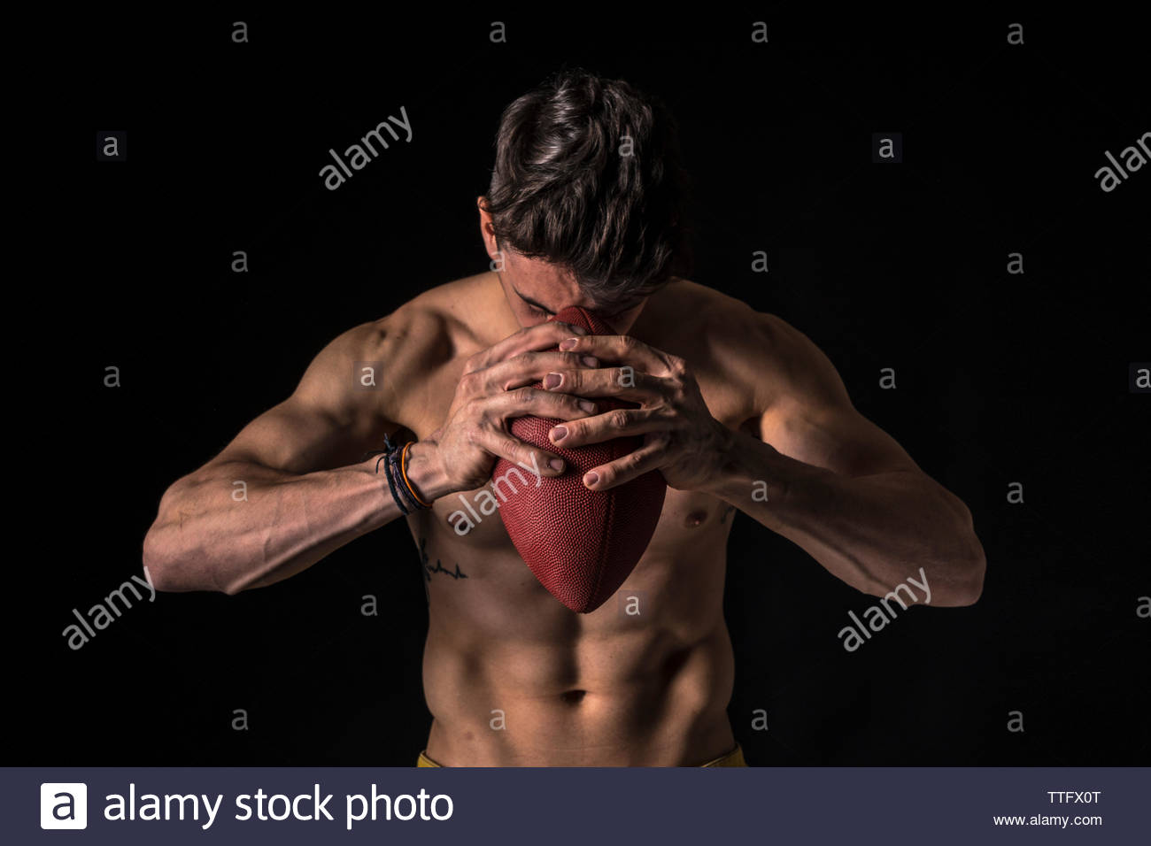 American football player with ball, abs, isolated  background - Stock Image