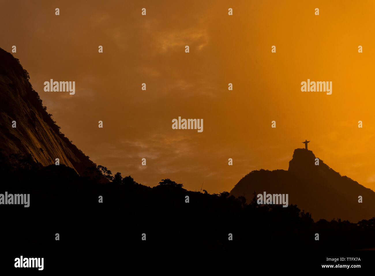 Beautiful orange sunset with mountains and Christ the Redeemer Stock Photo