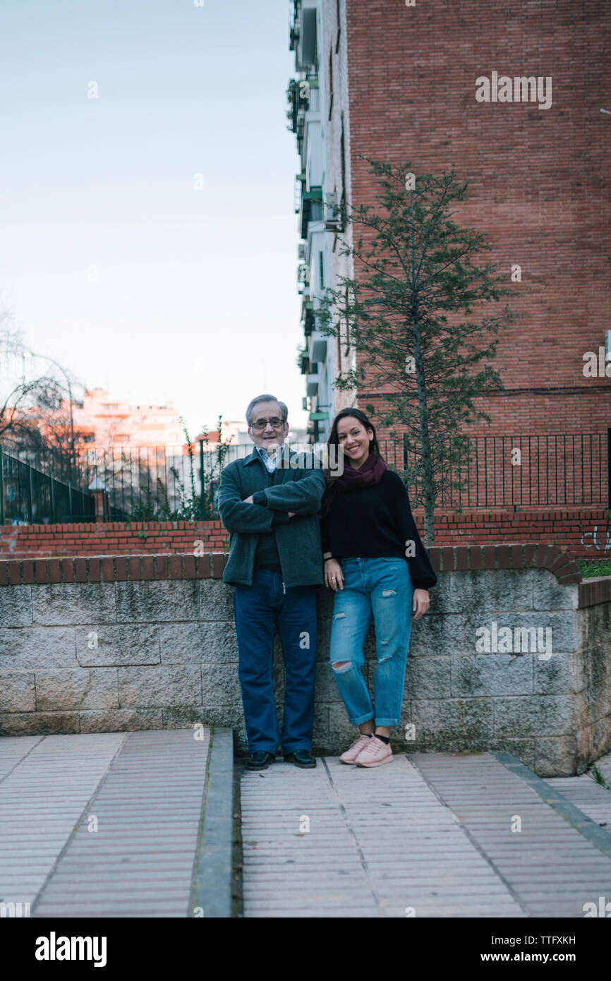 Father and daughter of adult age smile on the street Stock Photo