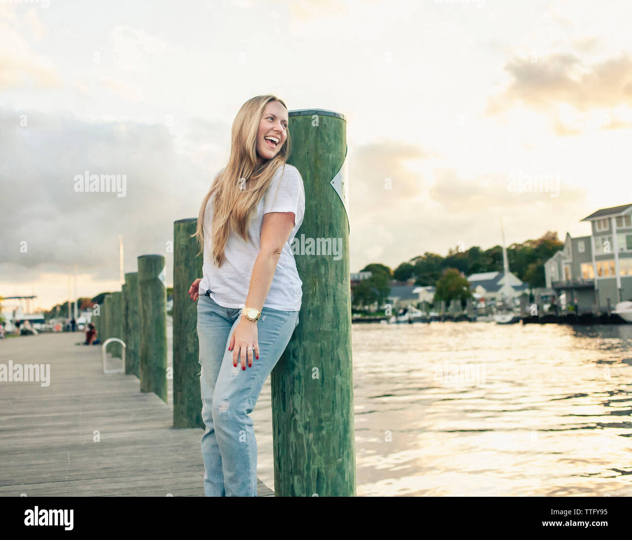 Happy woman screaming while standing on pier over river against sky during sunset Stock Photo