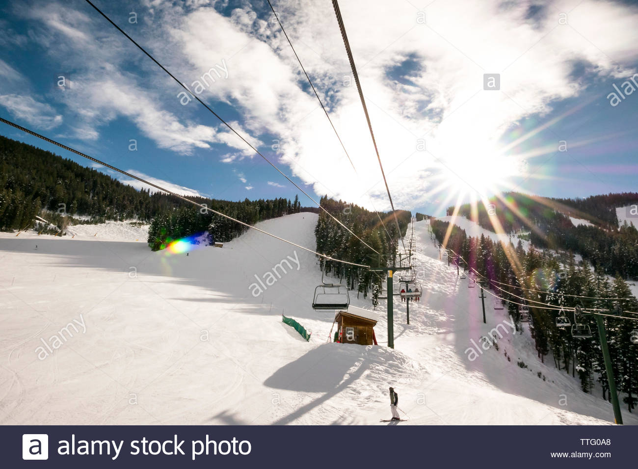 Ski lifts and skiiers on a sunny blue bird day in Sun Valley, Idaho. - Stock Image