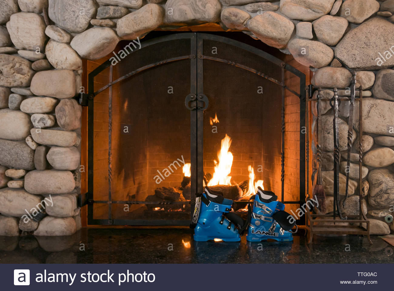 Ski boots warm and dry by the fire in the lodge at Sun Valley, Idaho. - Stock Image