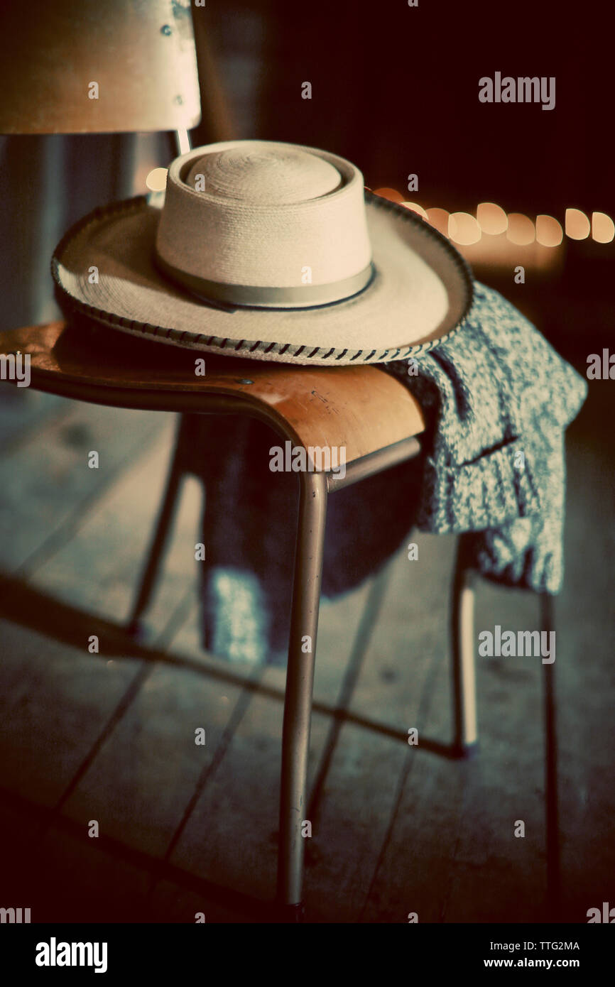 Close-up of hat and sweater on chair - Stock Image