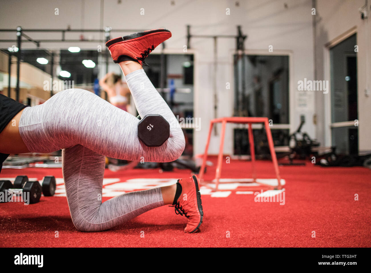 Woman lifts a dumbbell with her leg at the gym. Stock Photo