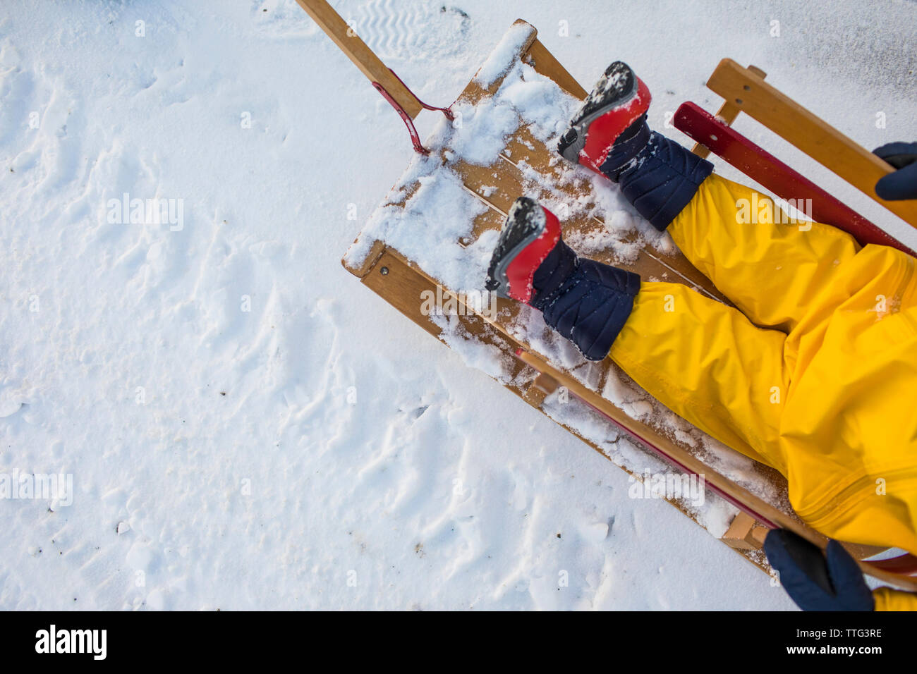 High angle of toddler sitting in wooden sled during winter. - Stock Image