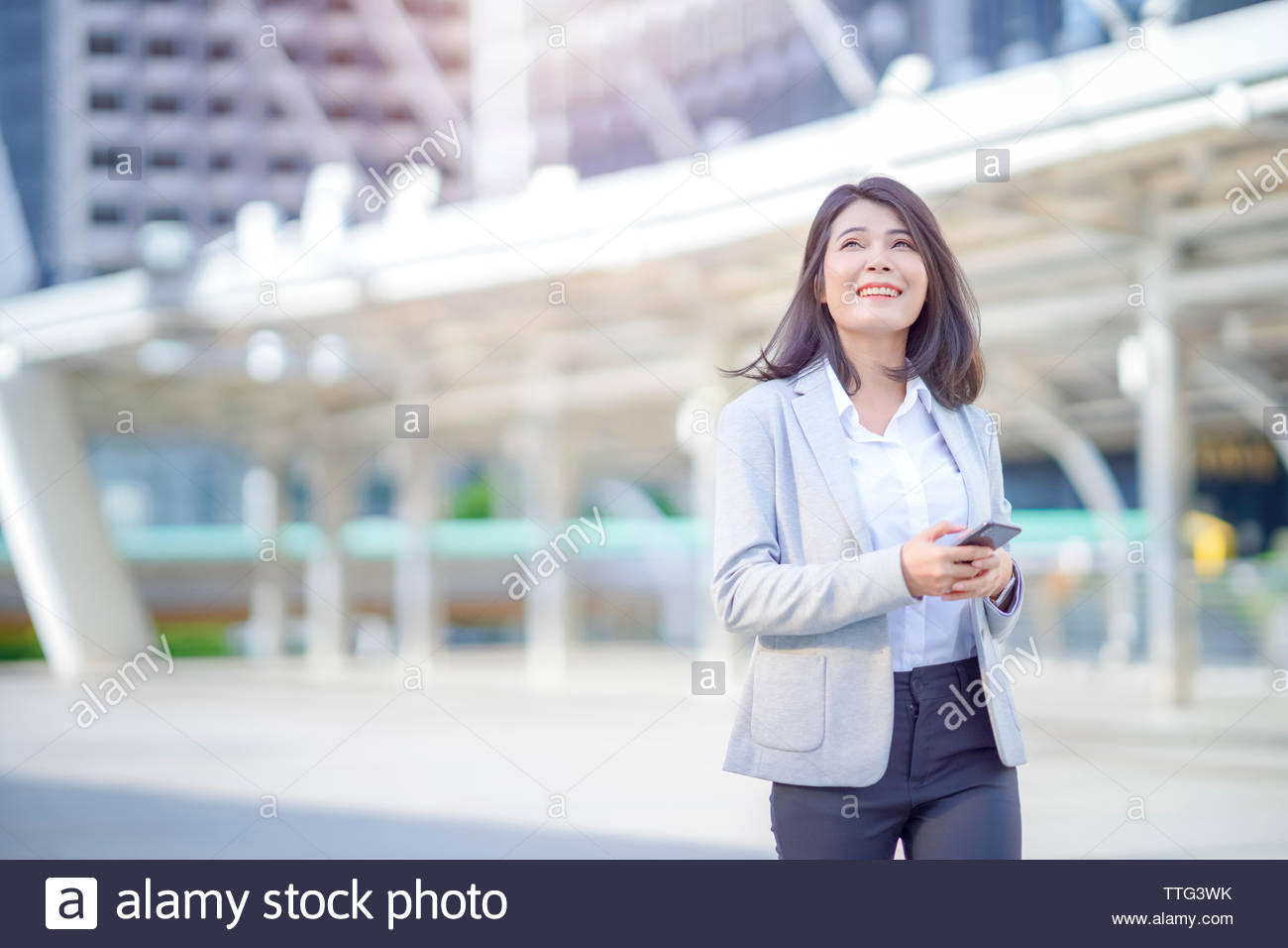 Asian businesswoman wearing suit holding smartphone going to work early in the morning - Stock Image