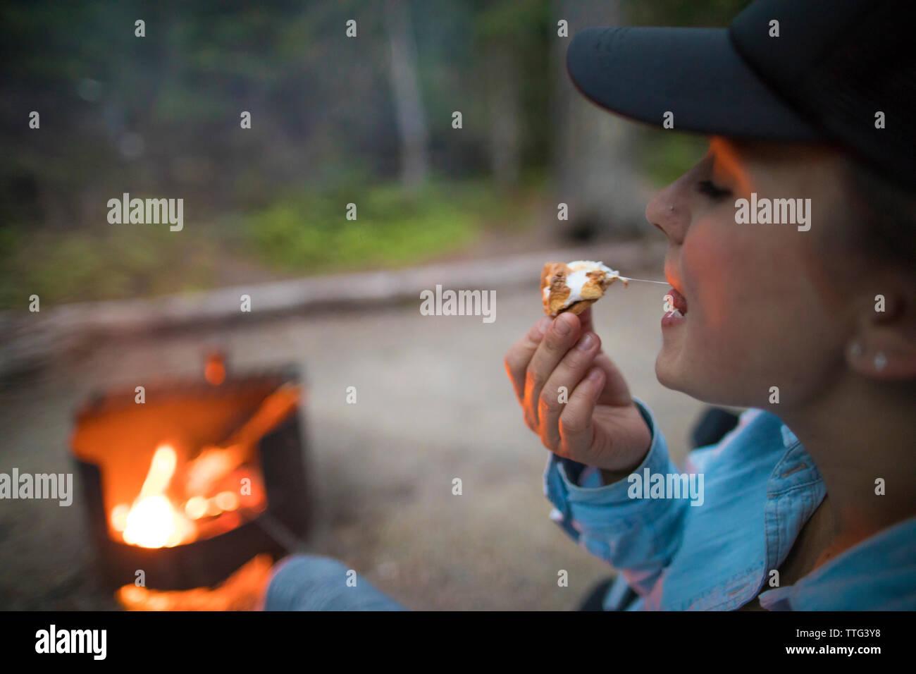 Woman eating smore while camping - Stock Image