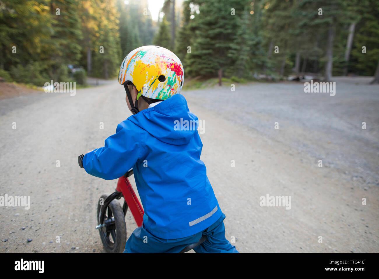 Toddler wearing helmet while biking outdoors. - Stock Image