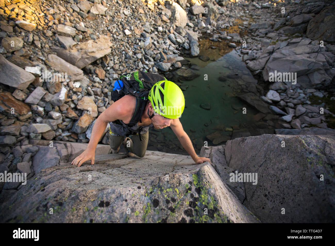 high angle of man bouldering above small alpine tarn. - Stock Image