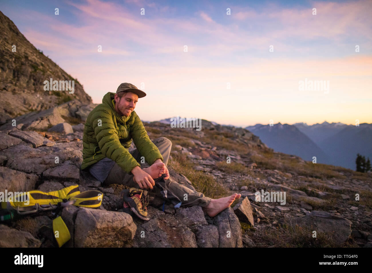 Climber takes his shoes off after a long day in the mountains. - Stock Image
