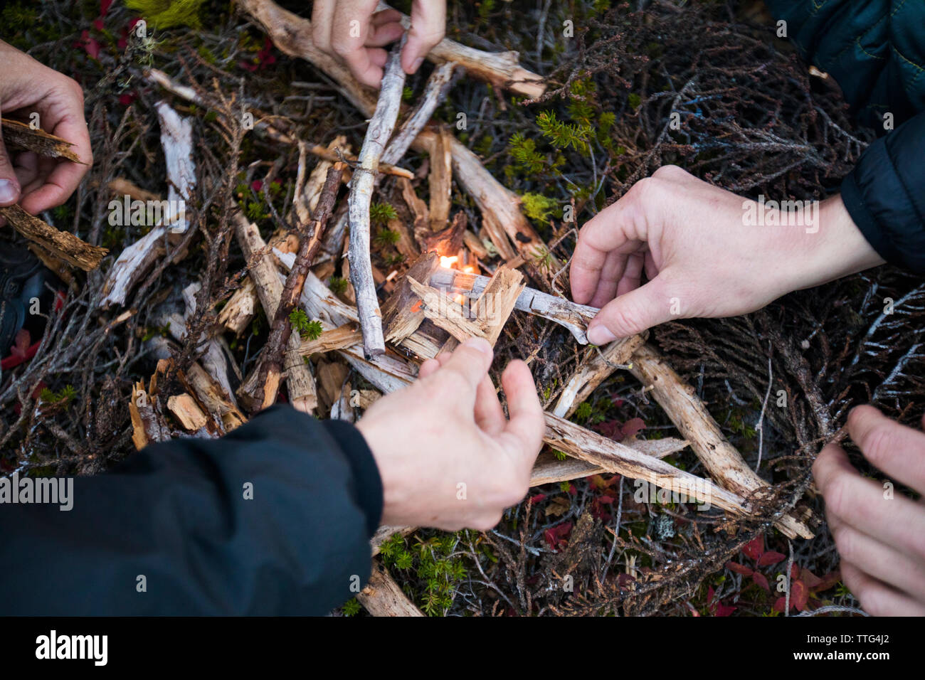 Many hands work to light a fire outdoors. Stock Photo