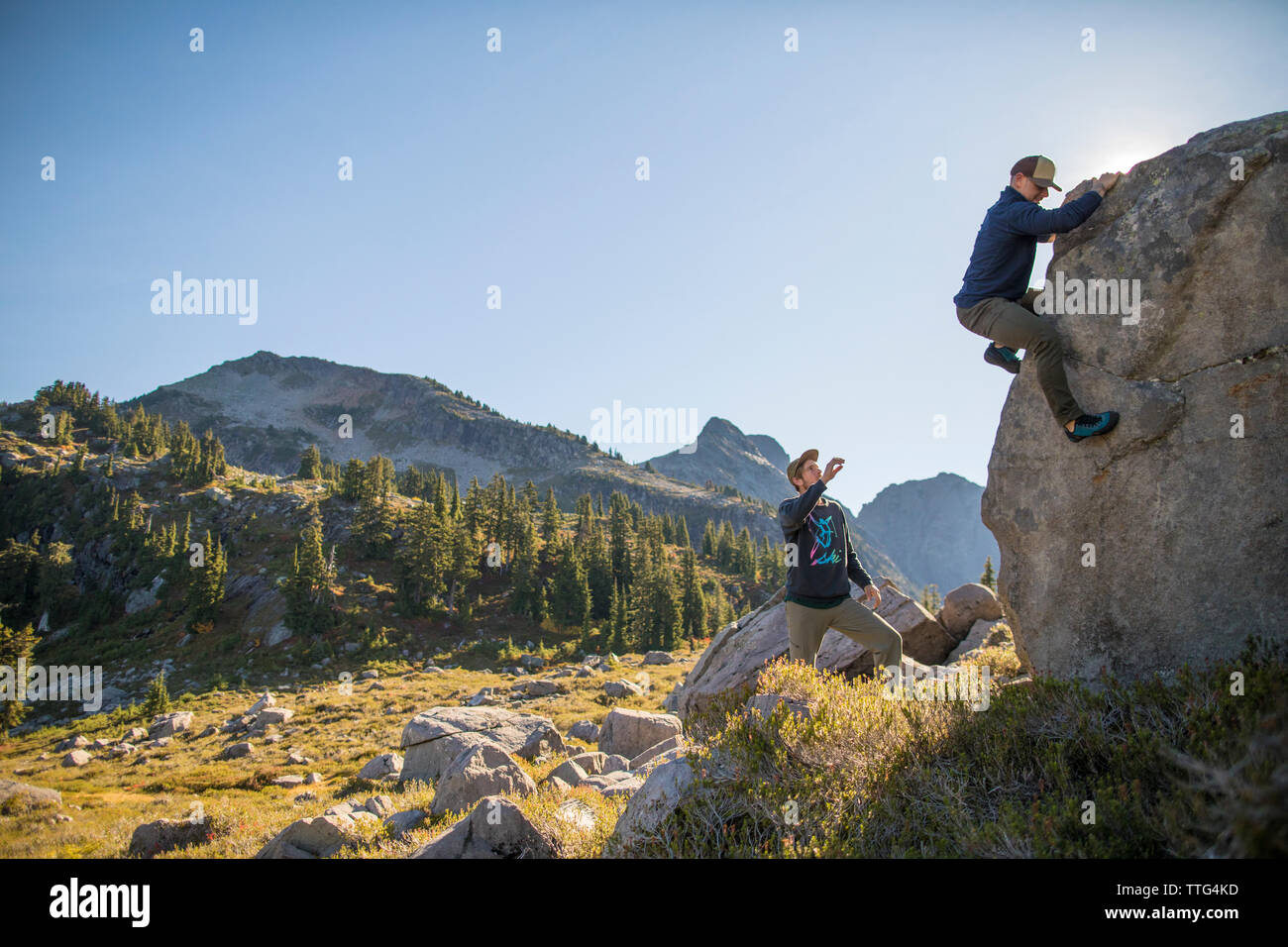 Climber bouldering on large rock with spotter below. - Stock Image