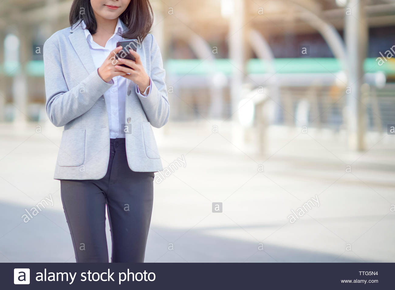 businesswoman reading email on smartphone while working in the city - Stock Image