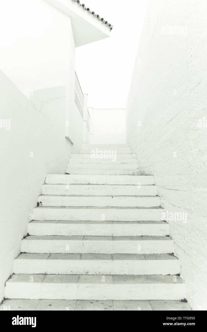 a white stone staircase next to a white wall and a white building - Stock Image