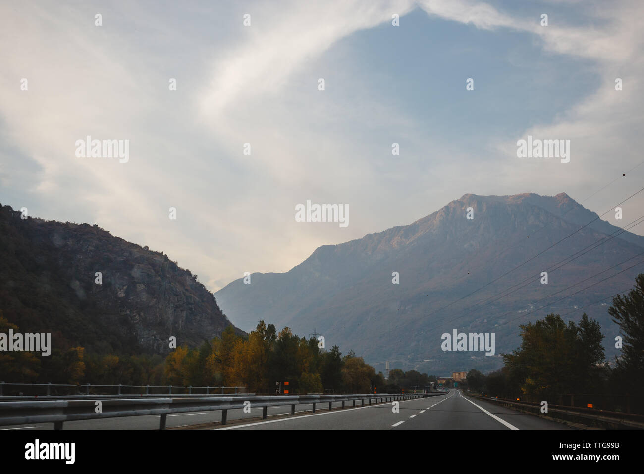 A deserted highway with mountains in the background and a dramatic sky - Stock Image