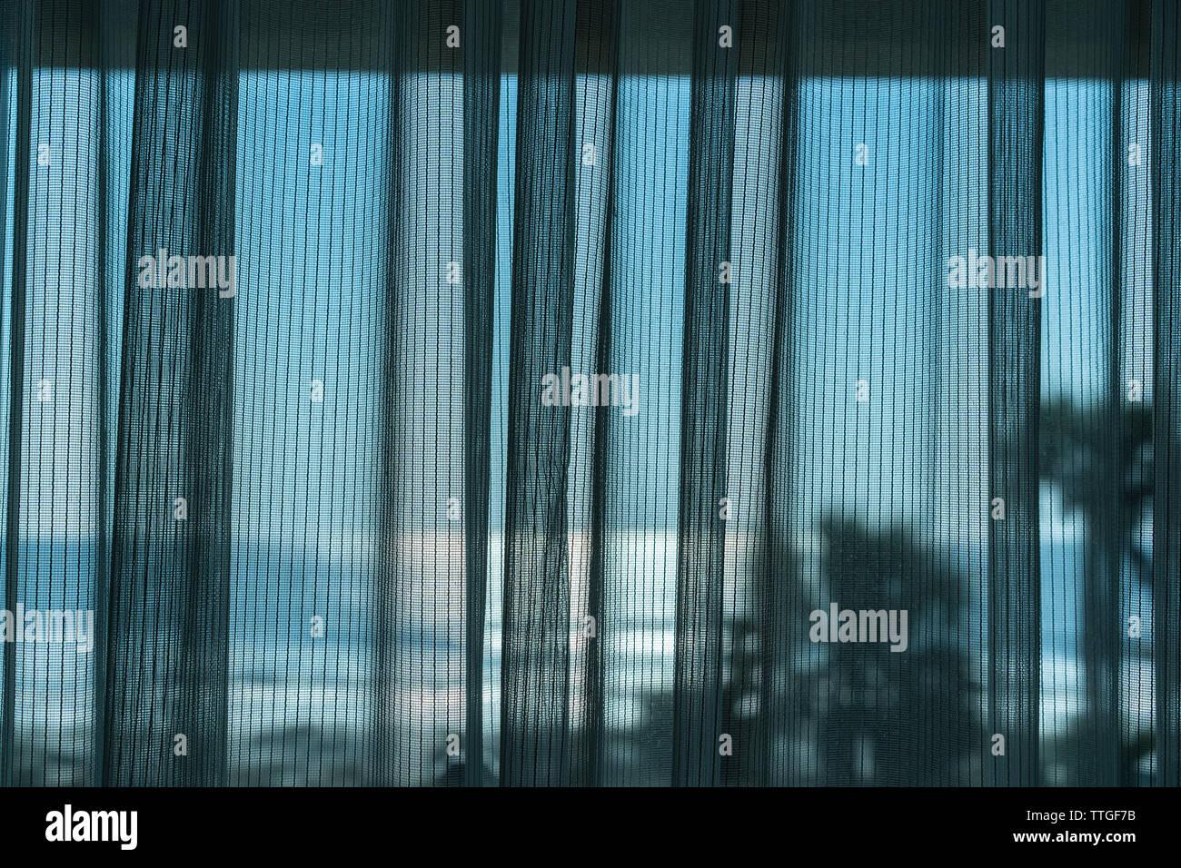 Mesh curtain drawn across window of hotel room overlooking the ocean - Stock Image