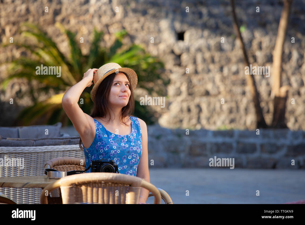 Young attractive cheerful travel girl walking with camera in old town - Stock Image