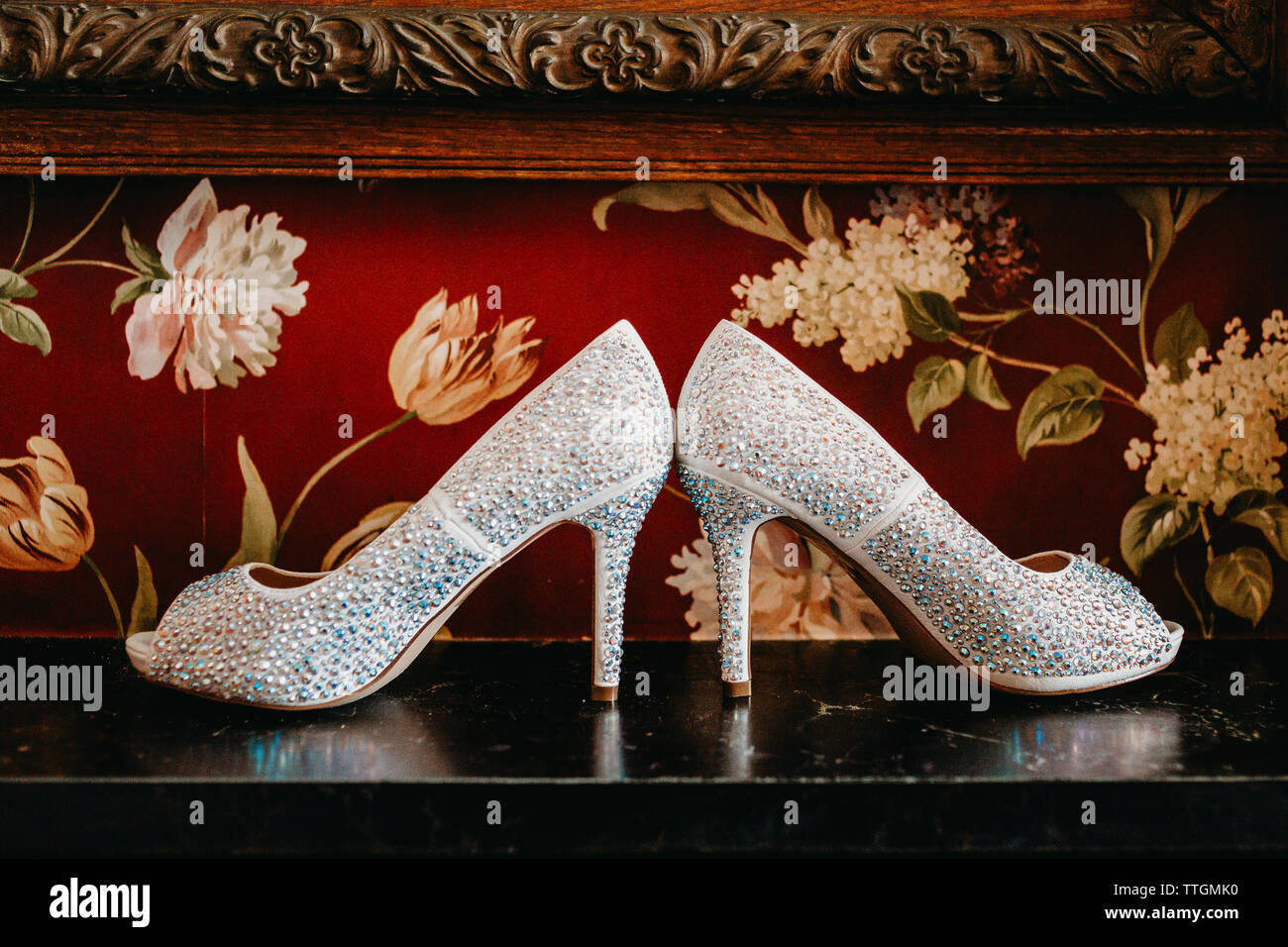 Brides shoes sitting on a black marble mantle with red wallpaper - Stock Image