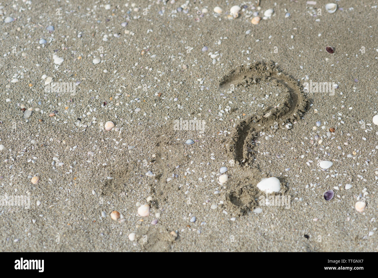 question mark wriiten on a sandy beach. Concept of faq, travel tips and travel destinations - Stock Image