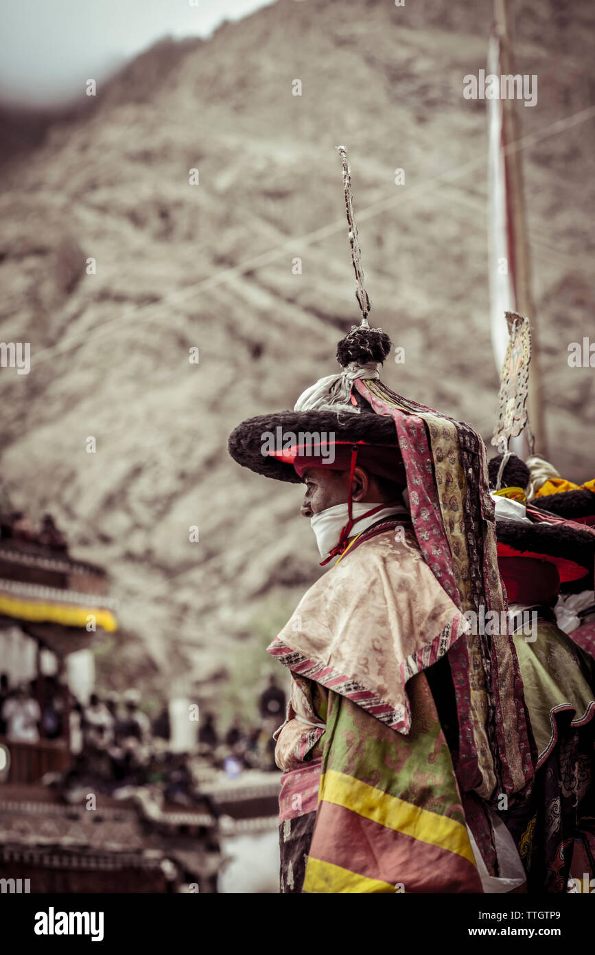 Male dancer in traditional clothing standing against mountain - Stock Image