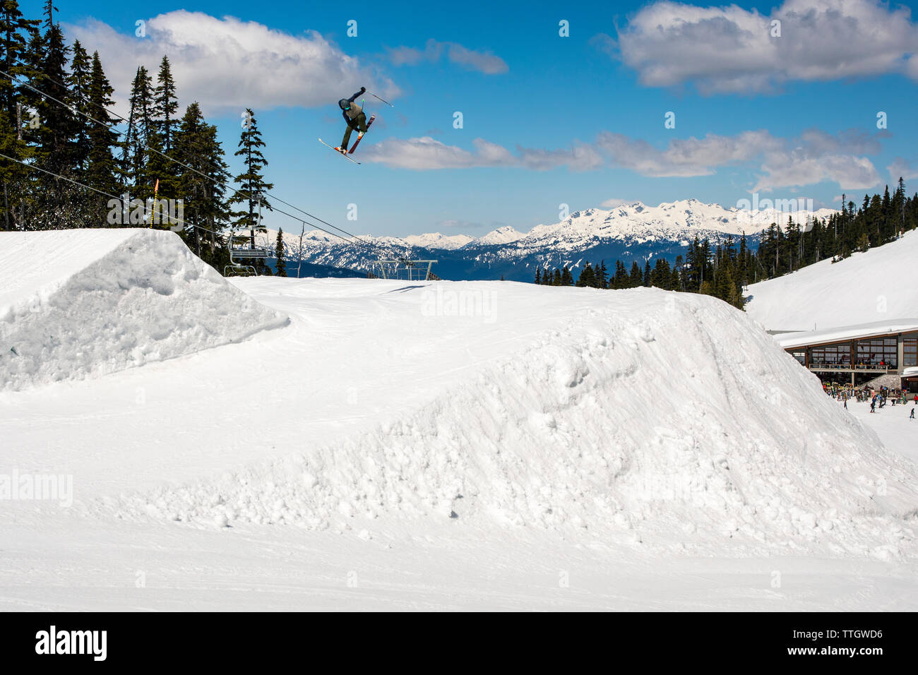 A man hits a jump on skis in the terrain park at Whistler Blackcomb. - Stock Image
