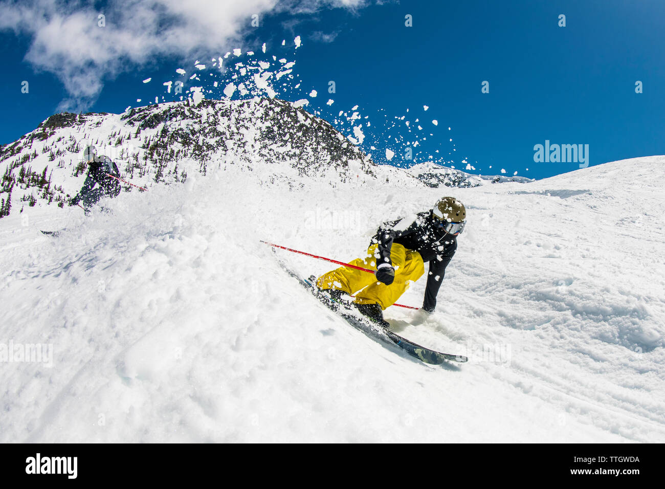 A man skis a banked course in the terrain park at Whistler Blackcomb. - Stock Image