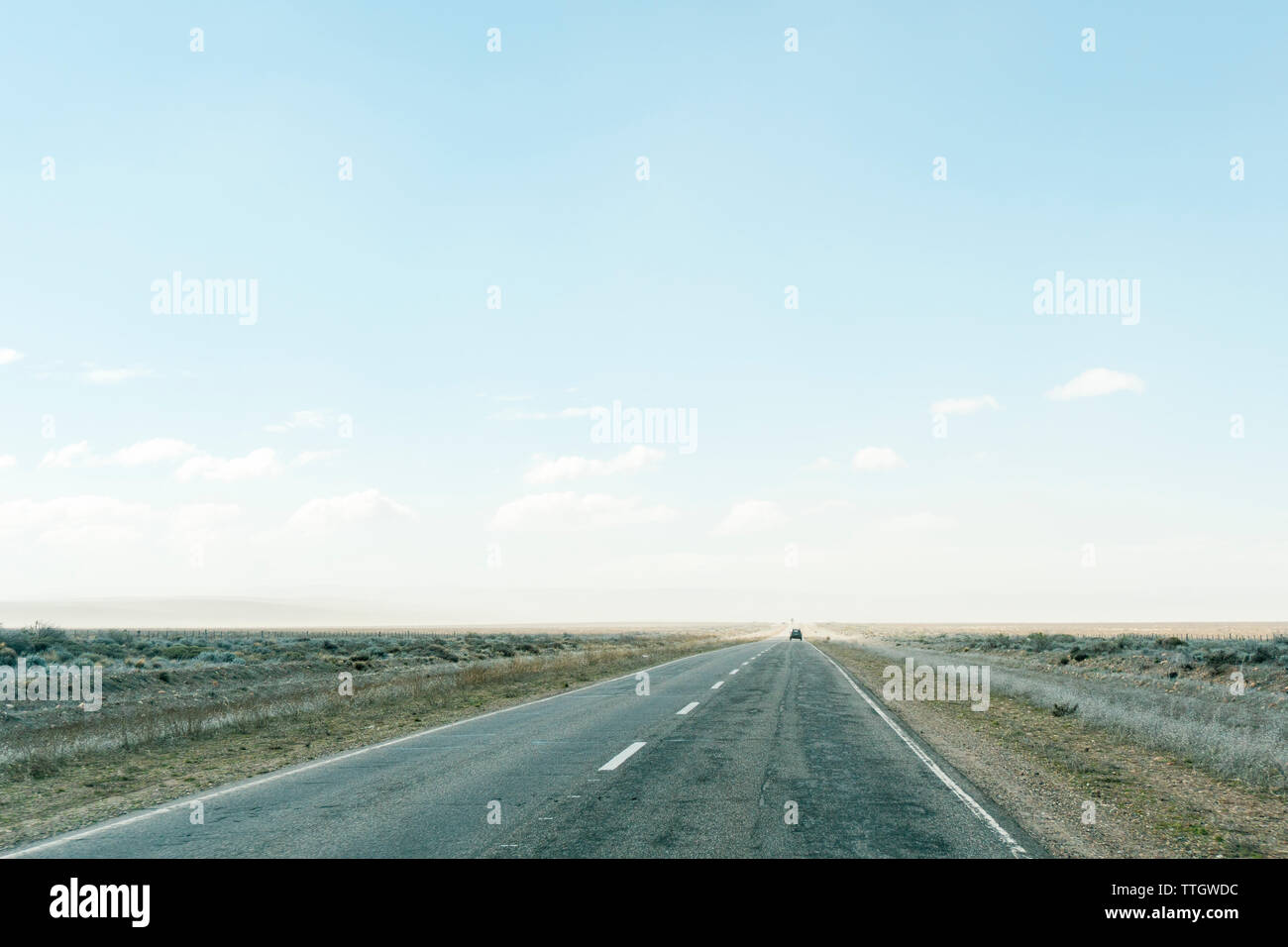 Driving along a remote flat road in Argentina on a sunny winter day. - Stock Image