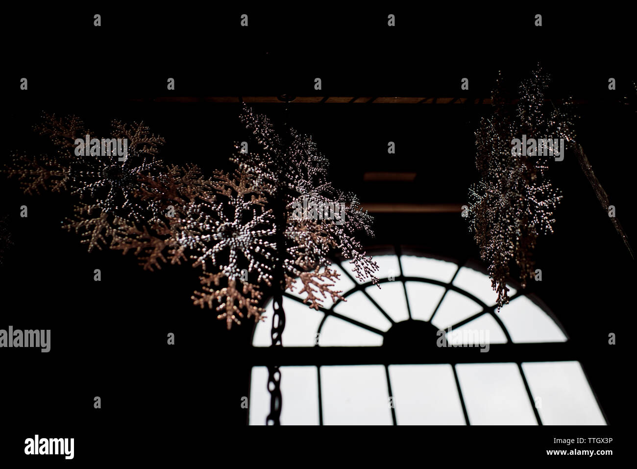 fake snowflakes hanging from the ceiling shinning in the light - Stock Image