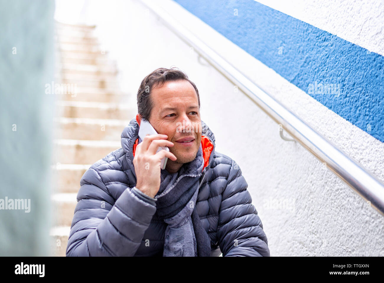 Man using a smartphone while sitting on a staircase outdoor. Stock Photo