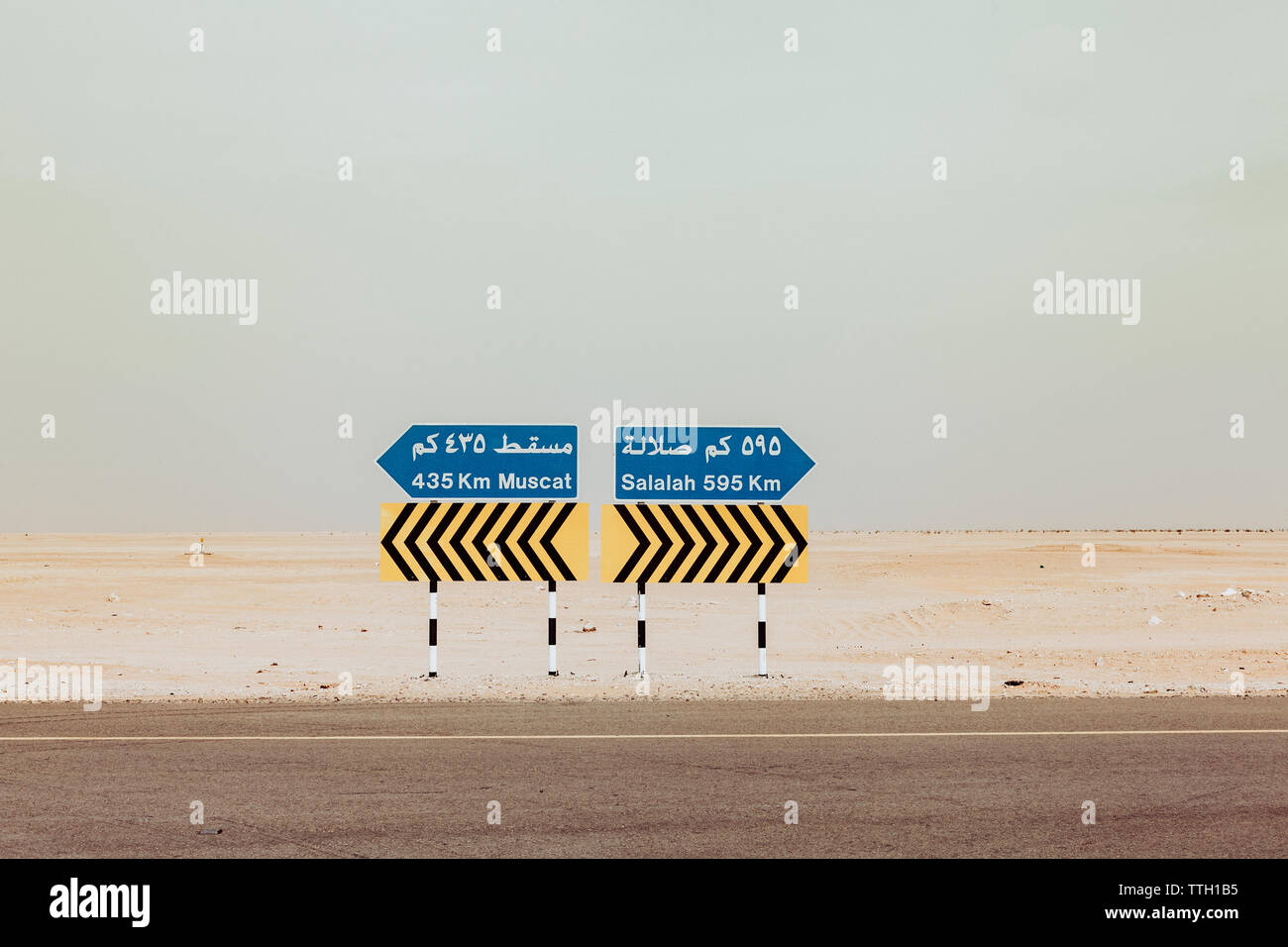 Signboards on desert against clear sky, Oman - Stock Image