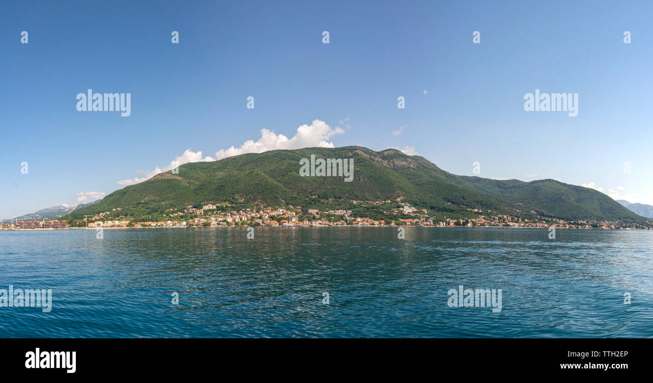 Small tourist villages on the Bay of Kotor in Montenegro, in a sunny summer day. The beginning of the cruise from Tivat city. - Stock Image